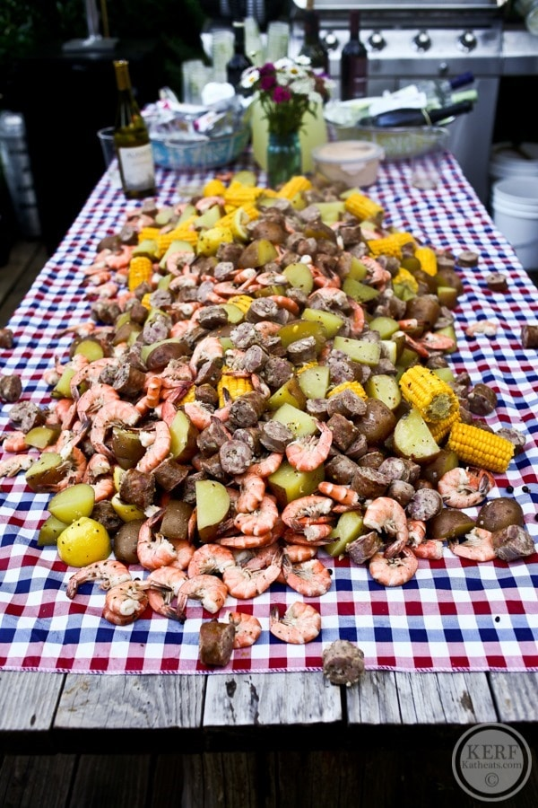 low country boil food spread over picnic table