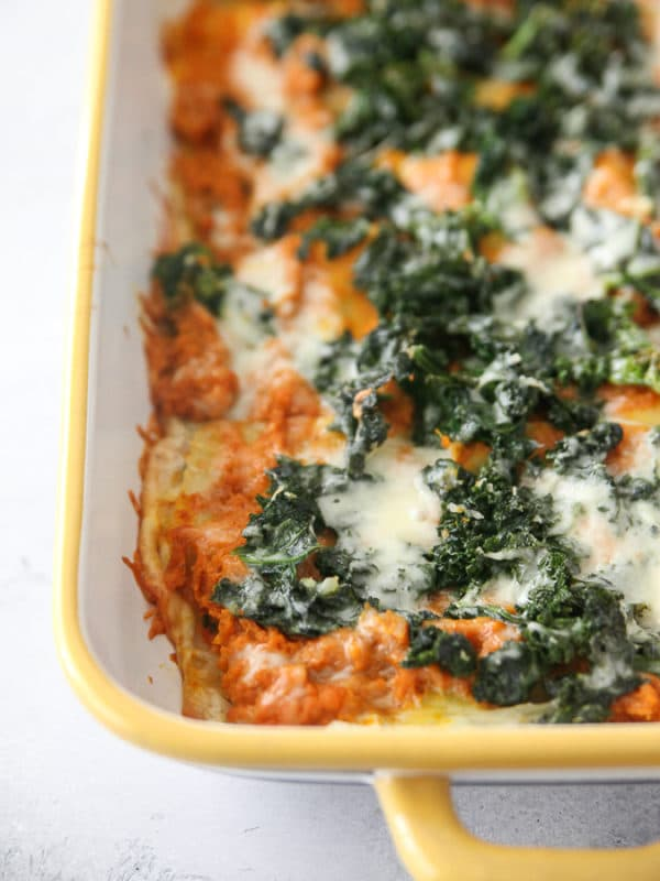 pumpkin, goat cheese and kale lasagna in a yellow casserole dish