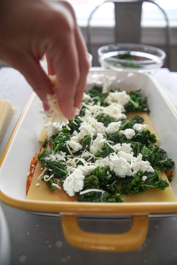 kale and goat cheese layer in a yellow casserole dish with a hand sprinkling shredded cheese
