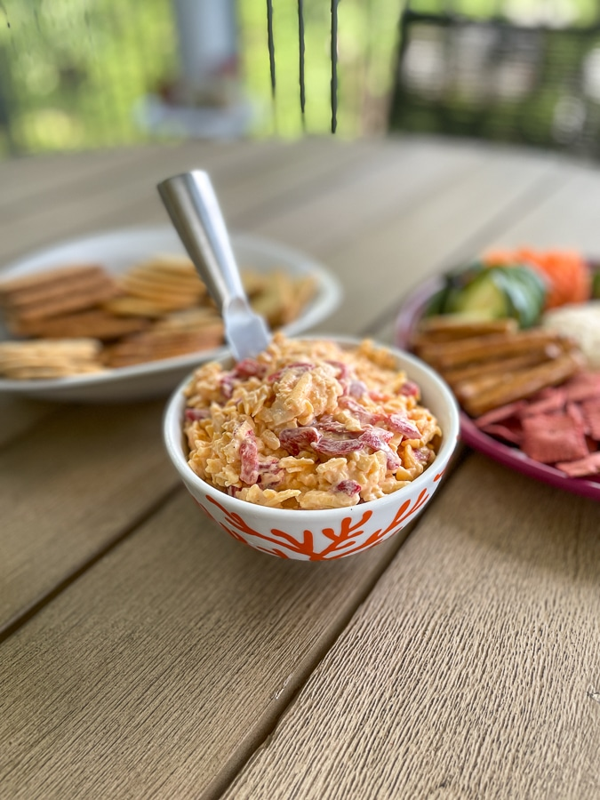 bowl of pimento cheese with greek yogurt and a silver spoon
