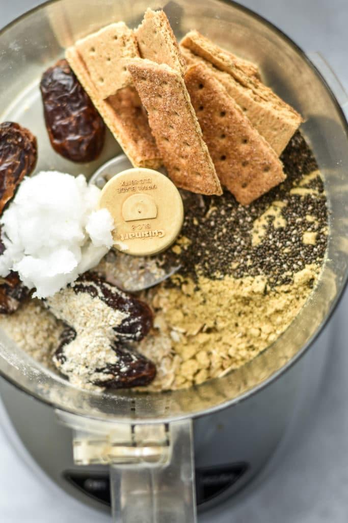 ingredientes en un procesador de alimentos como galletas Graham, aceite de coco y semillas de chía