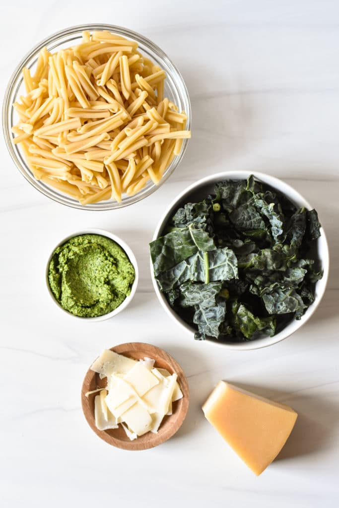 pasta kale pesto and parmesan cheese in separate bowls