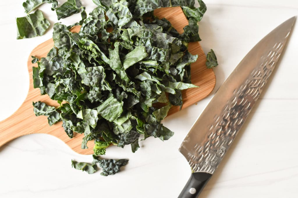 shredded kale on a cutting board with knife