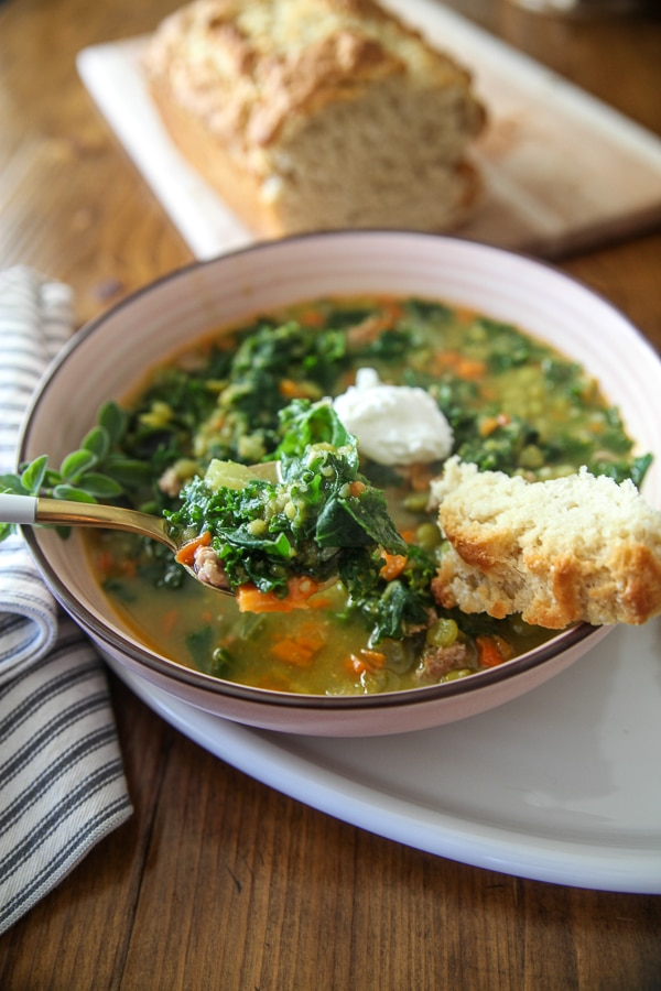 kale and pea soup on a spoon with crusty bread