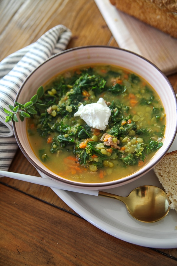 pea soup with greek yogurt and herbs in a pink bowl