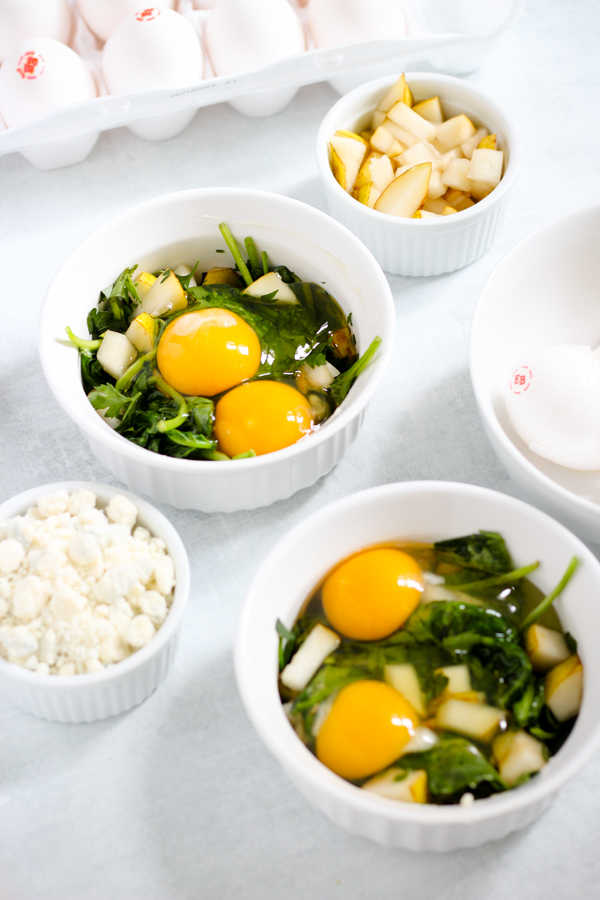 eggs cracked in ramekins with greens and ingredients