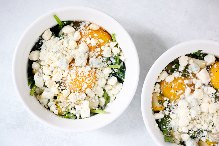 blue cheese sprinkled on top of eggs and greens ramekins