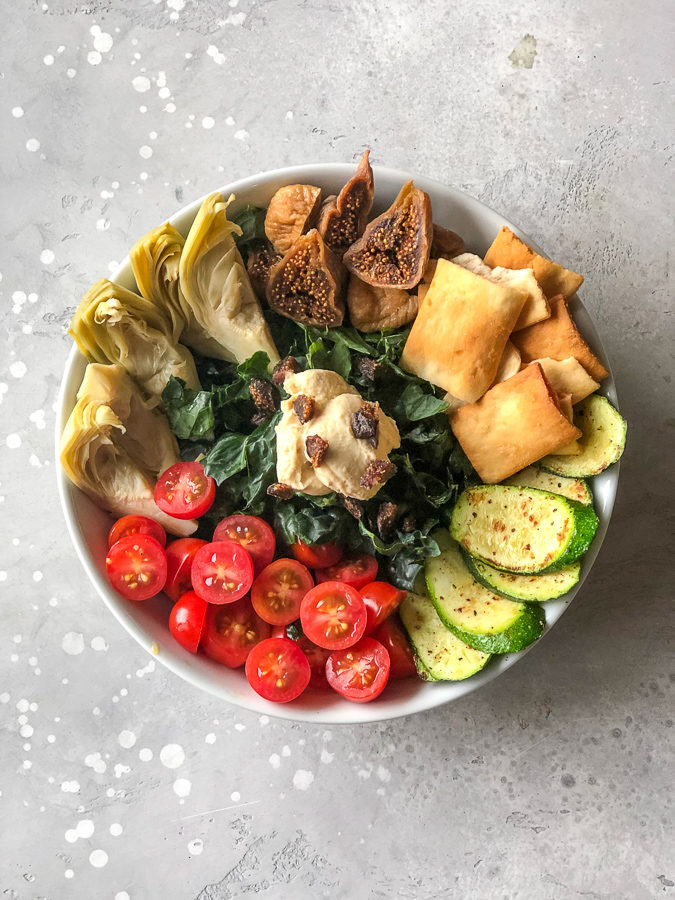 Mediterranean salad Bowl with figs, artichokes, pita chips, cucumber, hummus, tomatoes