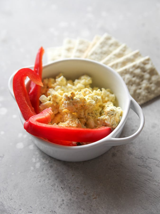 egg salad with red peppers in a white bowl