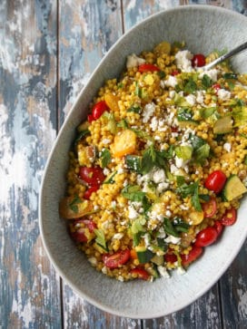 Couscous salad with zucchini, tomatoes, parsley, and feta