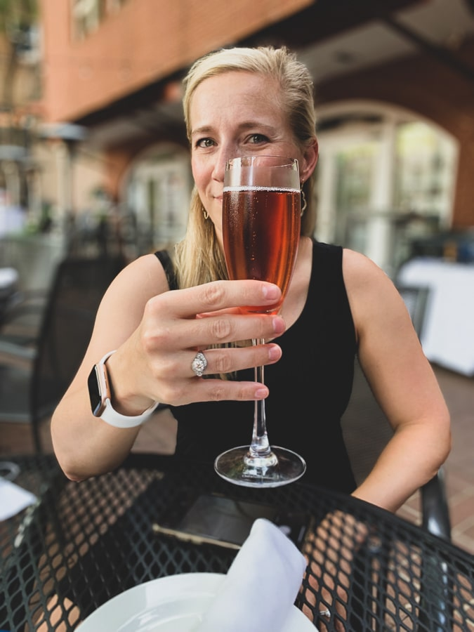 kath drinks champagne in charlottesville patio