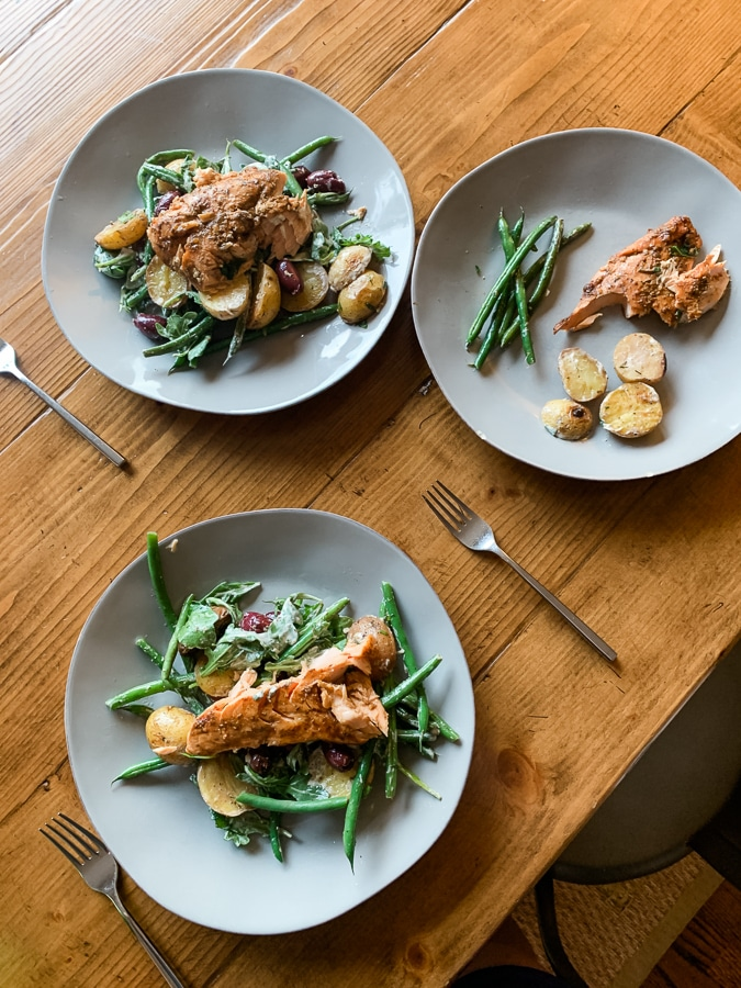 dinner plates with salmon, green beans, and potatoes