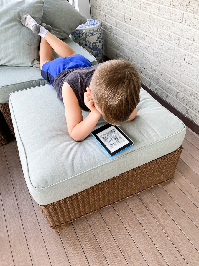 child reading kindle on ottoman