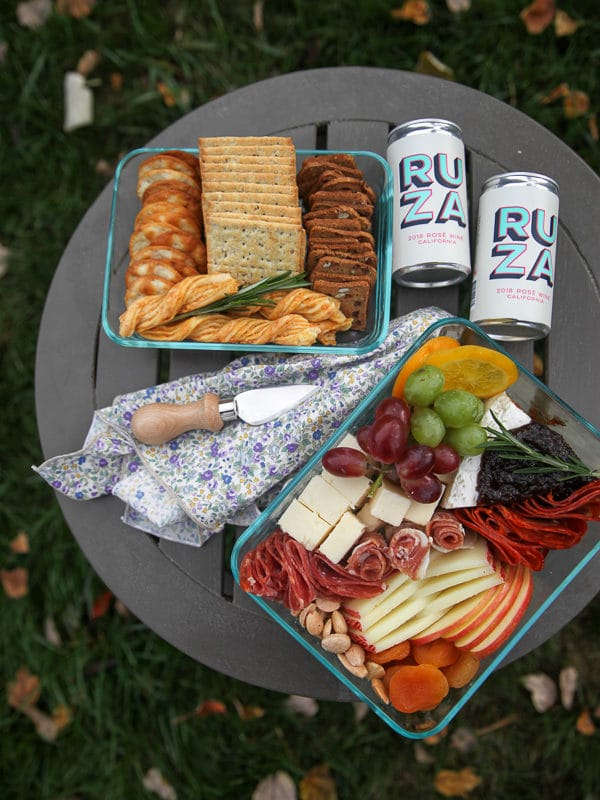cheese and fruit in a glass container with crackers and cans of wine