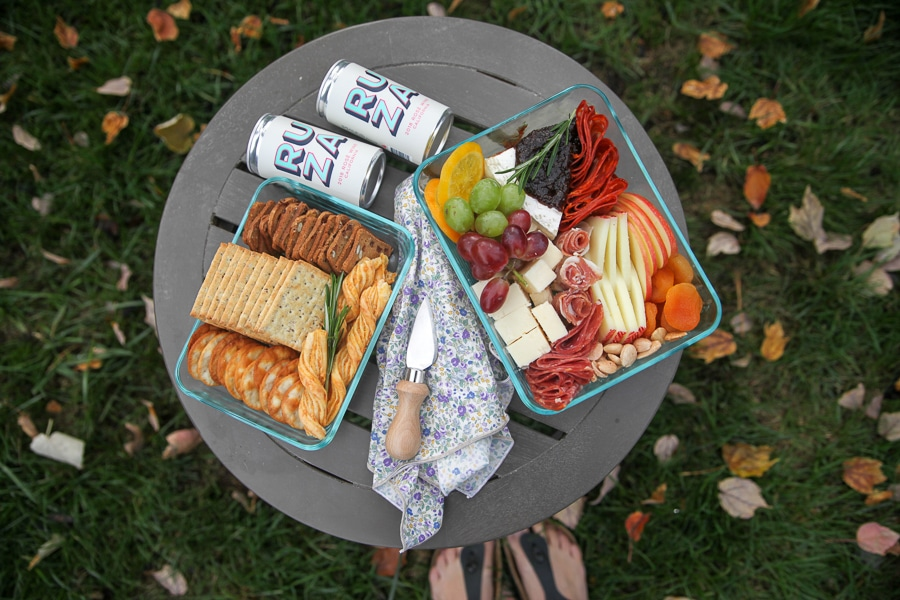 picnic cheese board from above with crackers, cheese straws and wine
