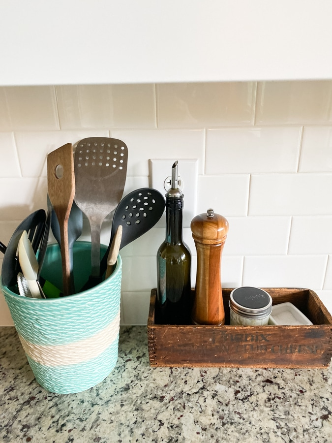 organized kitchen utensils in an aqua beachy holder and condiments in a wooden vintage box