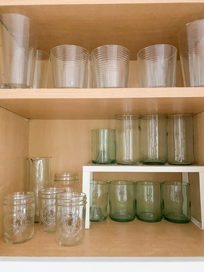 glasses in a cabinet using a shelf riser