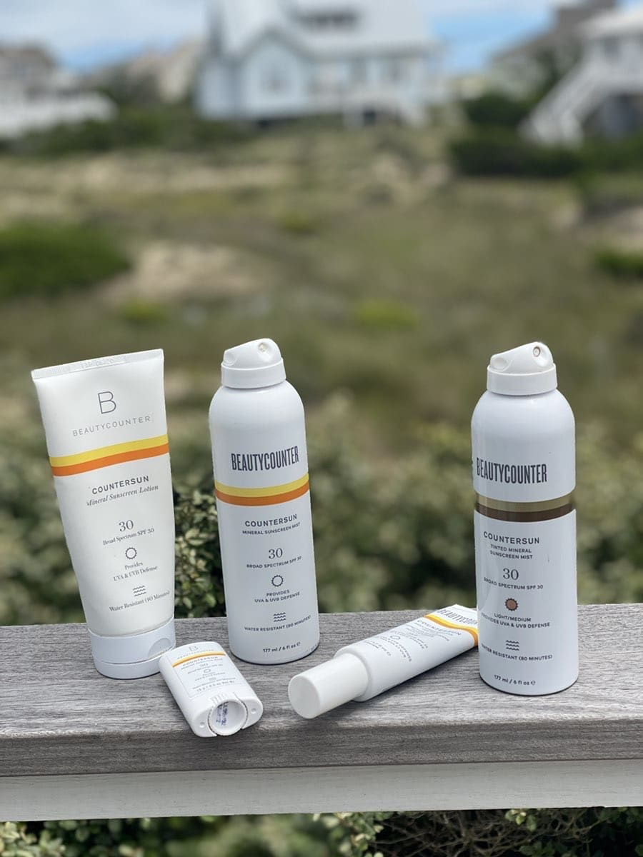 all of the beautycounter sunscreens on a deck railing