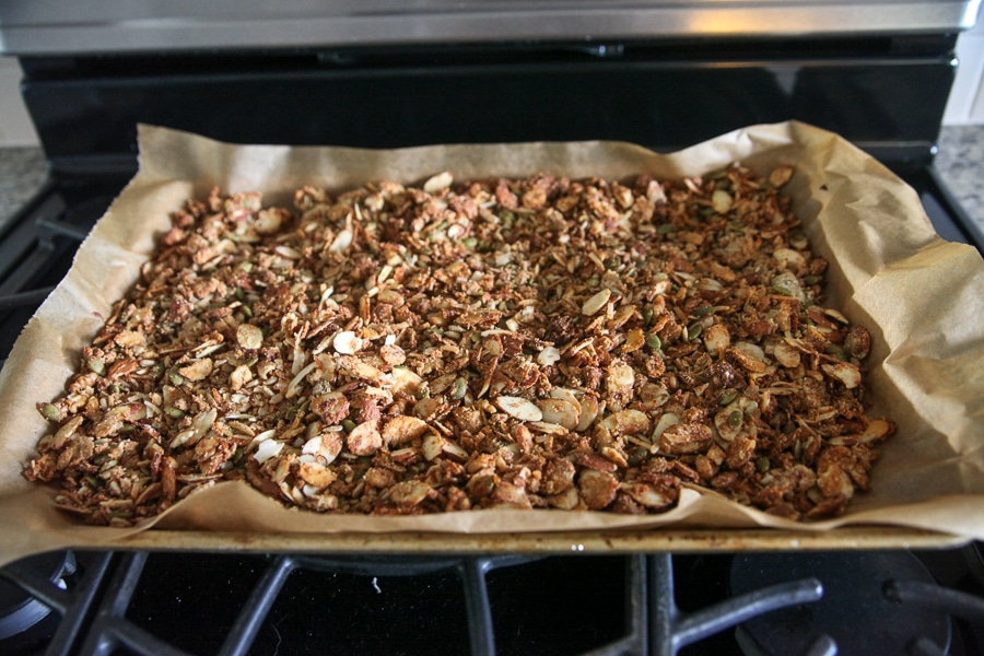 toasted granola on a sheet pan coming out of oven