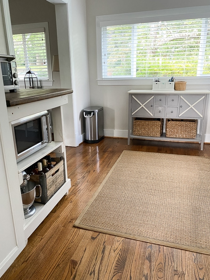 Natural jute rug on hard wood floors in dining area.