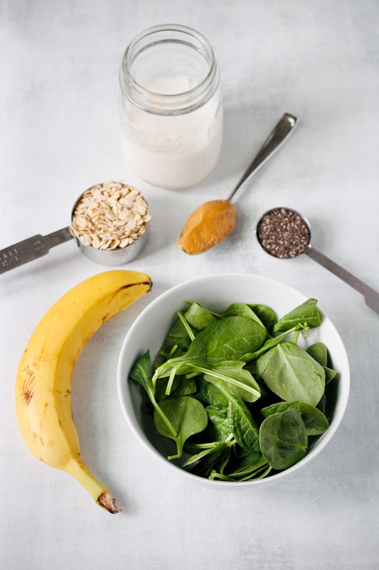 Overhead shot of measured smoothie ingredients: milk, oats, peanut butter, chia seeds, banana, and spinach.