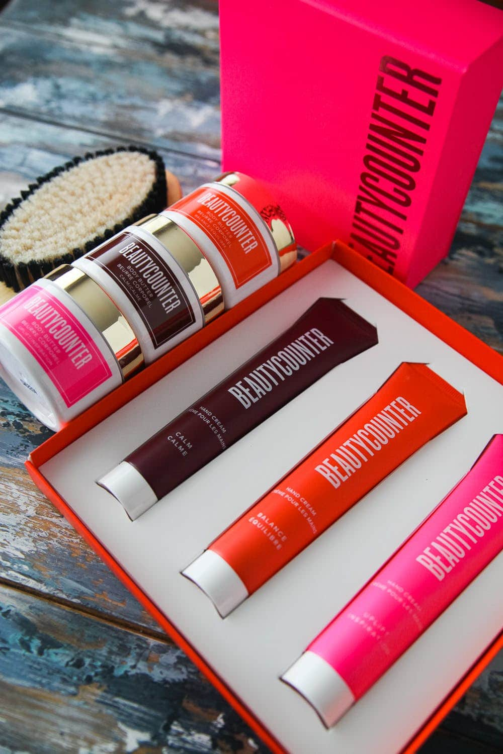 Beautycounter's Good Scents Body Butter & Hand Cream Trios in red and pink gift boxes.