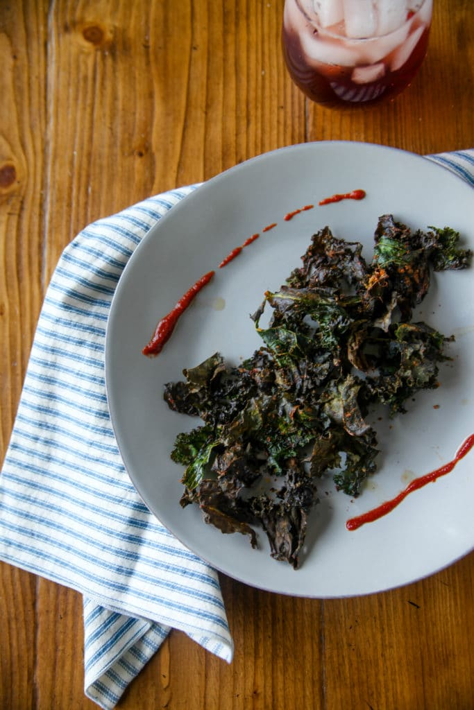 kale chips on a plate with sriracha