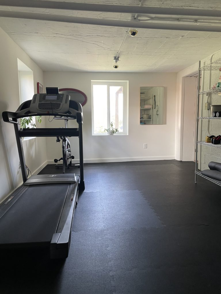 fitness room with treadmill and bike after