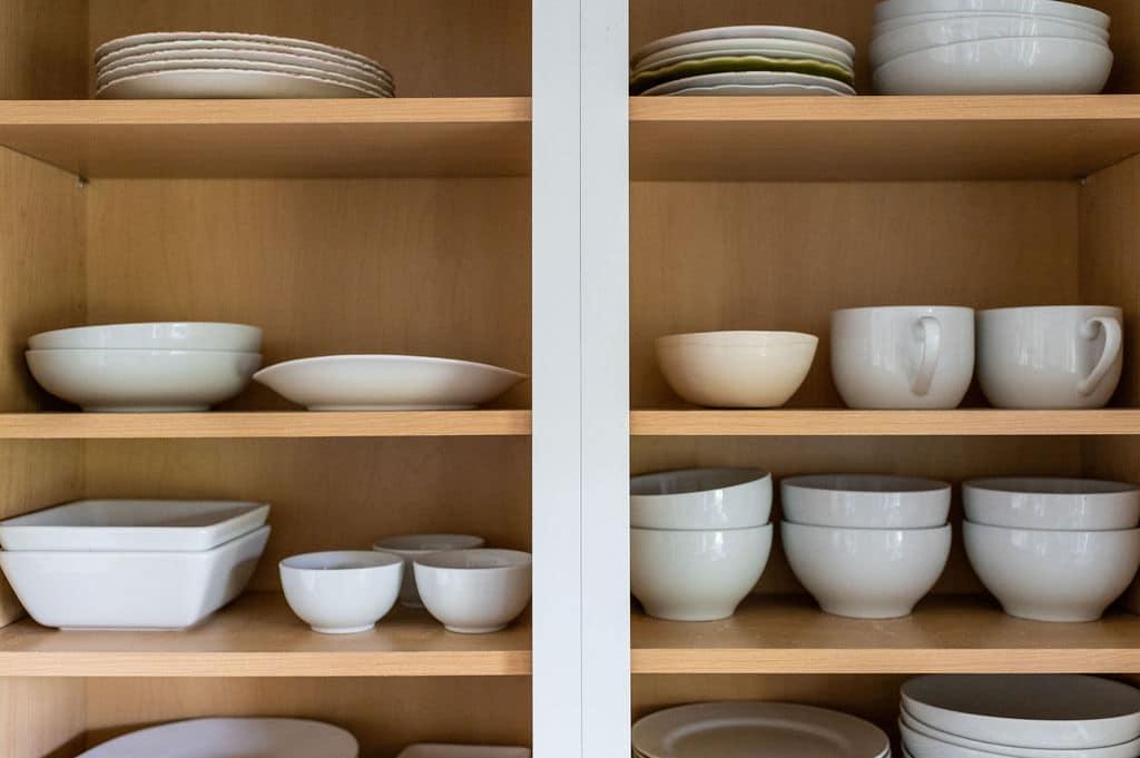 Organized white dishes in kitchen cabinet.