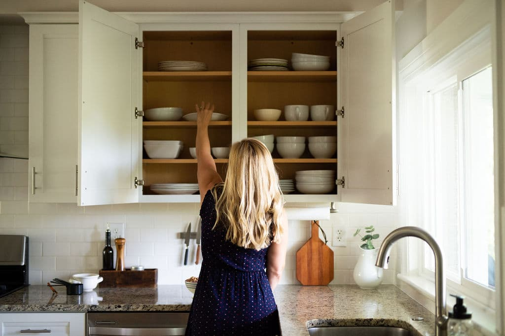 Kath Younger in kitchen grabbing a white dish from cabinet.