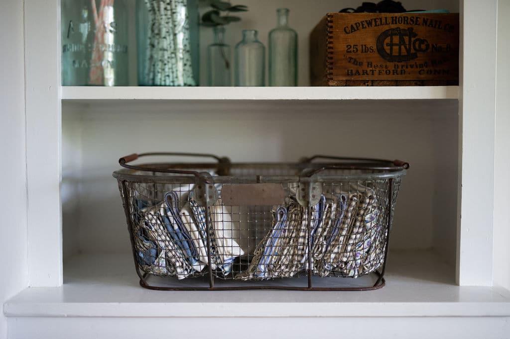 Estante organizado con decoración y cesto de rejilla con mantelería.