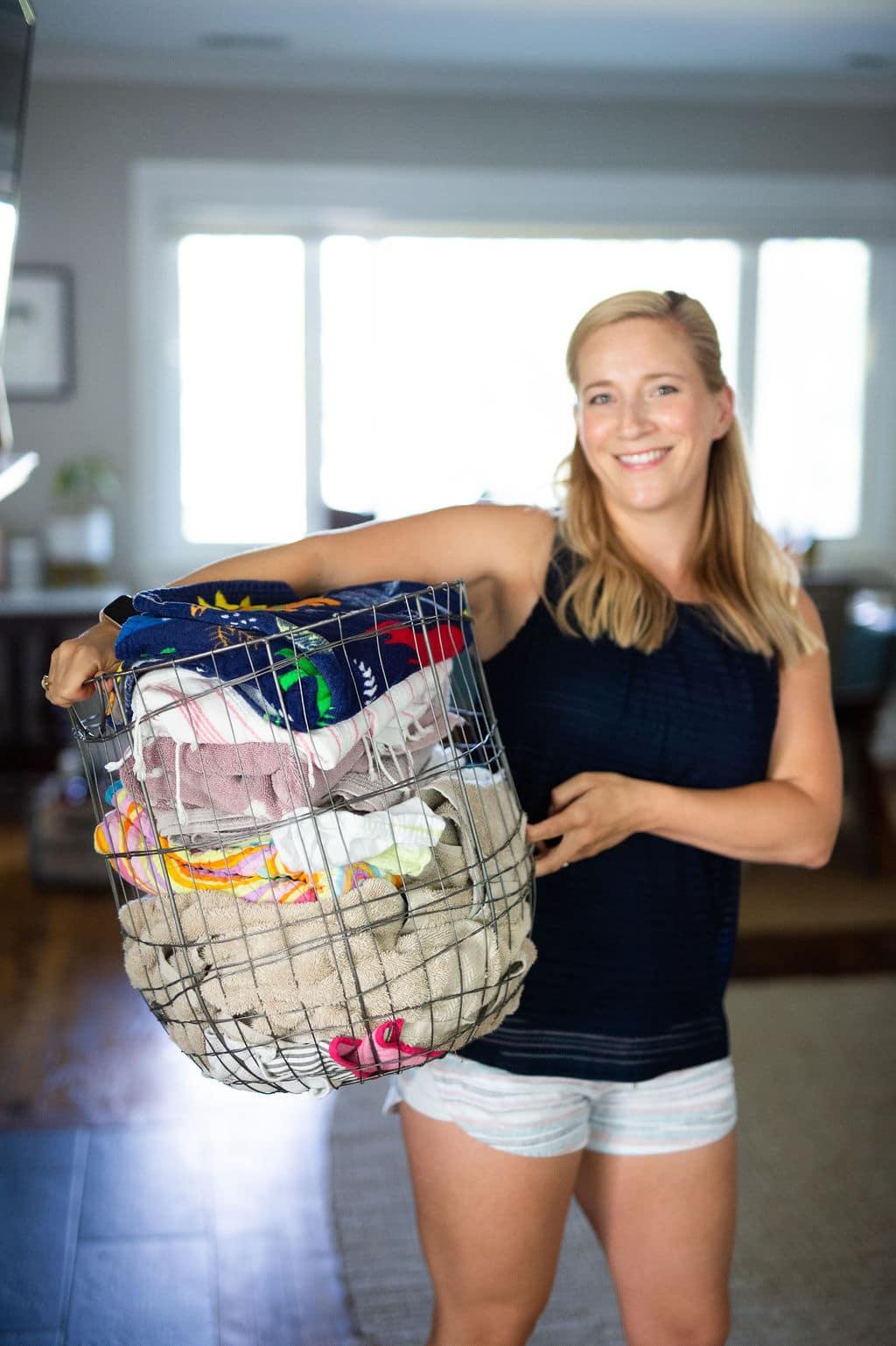 Kath Younger sosteniendo una canasta de alambre llena de ropa sucia.