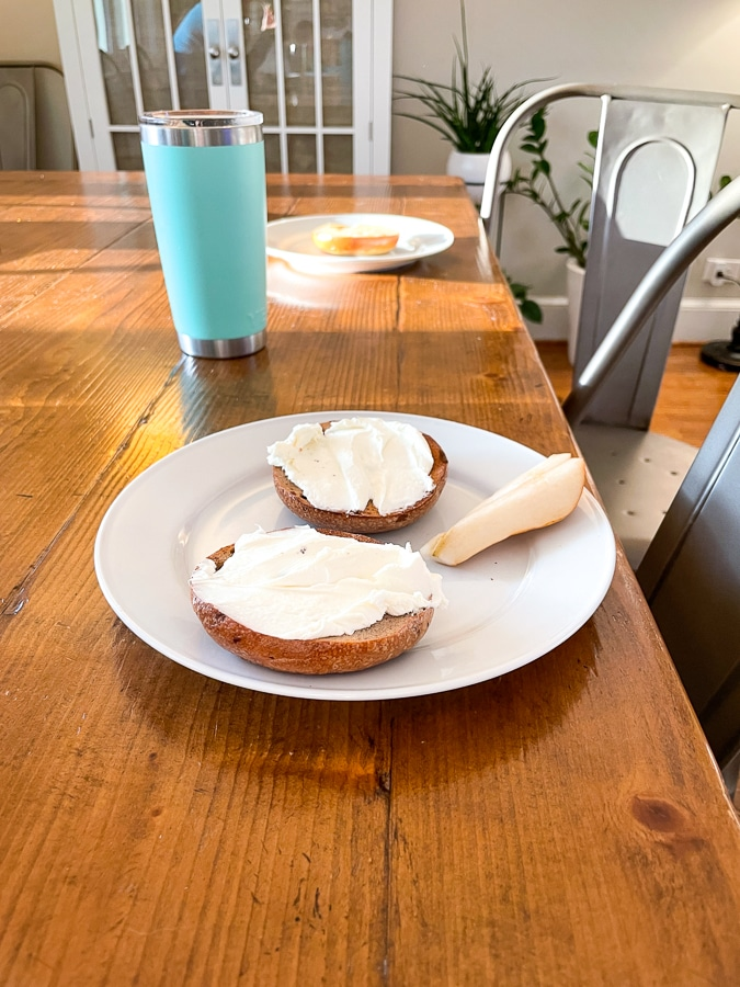 bagels on a table with white plates and coffee