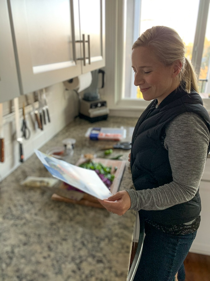 Kath reading a blue apron recipe card in her kitchen