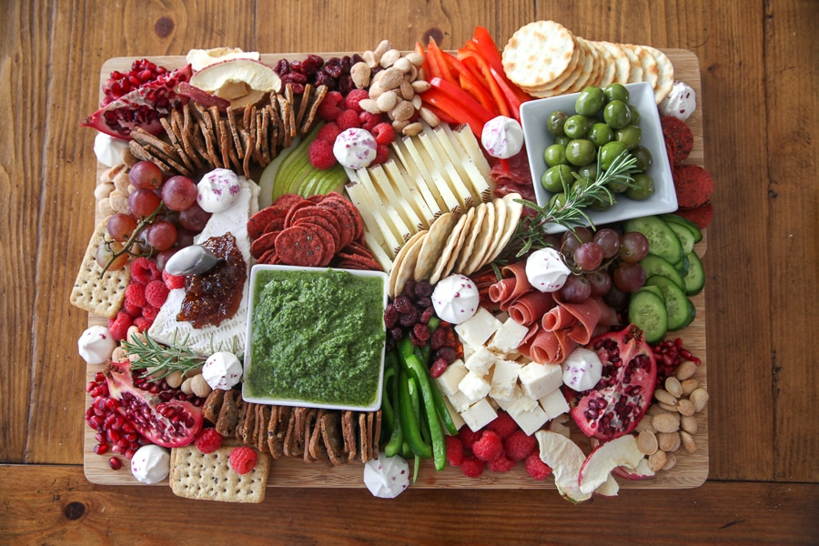 finished cheese board with cheese, meats, fruits, veggies, nuts, dips, crackers, meringues