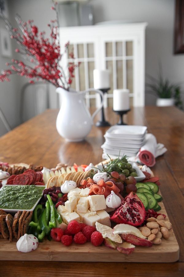 charcuterie board on a table with red berries in a pitcher and a stack of plates