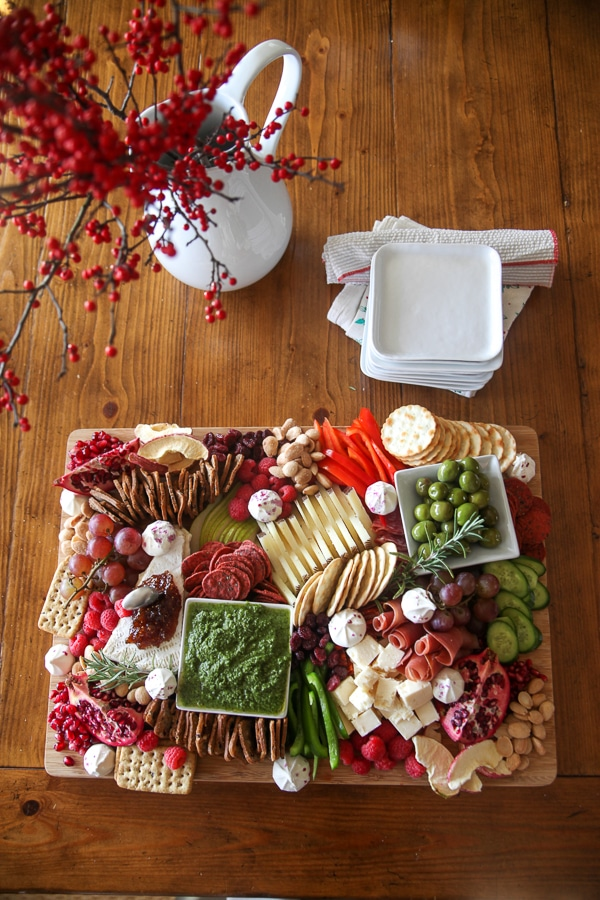 christmas charcuterie board with red berry branches in a white pitcher with plates on red napkins