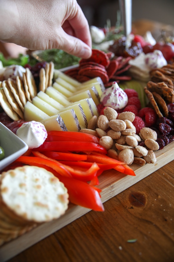 zoom in of red peppers, almonds, and sliced manchego on a cheese board