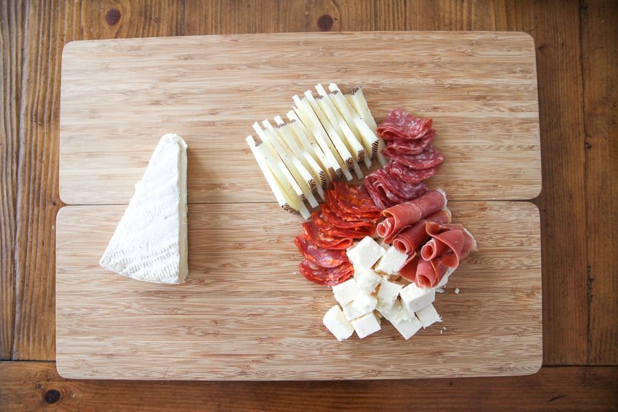 cheeses and meats on a cutting board
