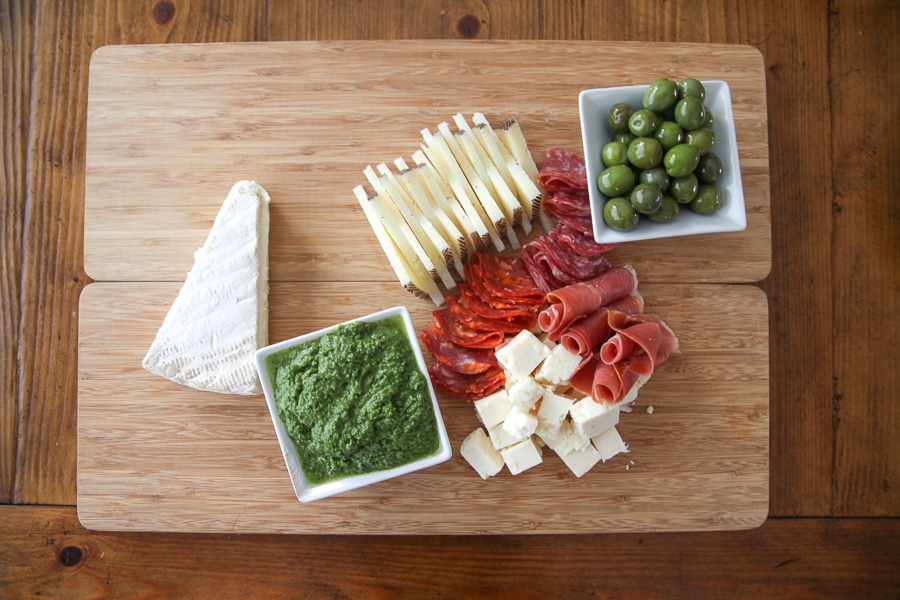 cheese, meats, and green olives with pesto dip