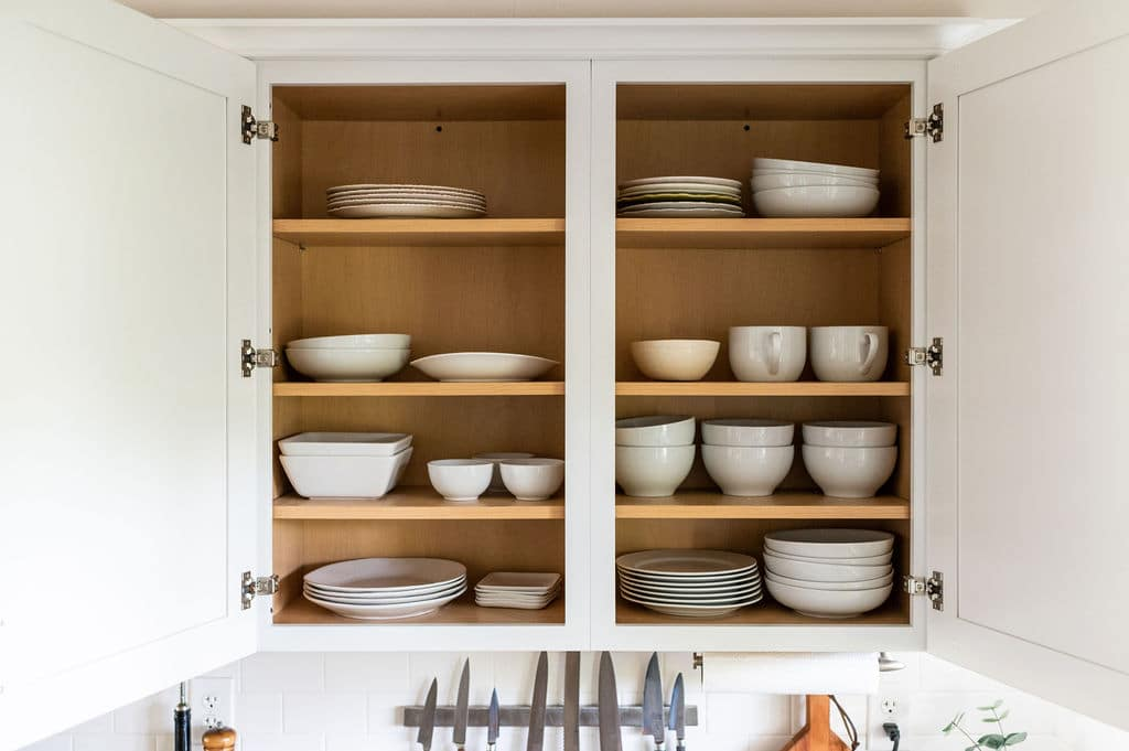 Open kitchen cupboards with white stacks of white plates and bowls.