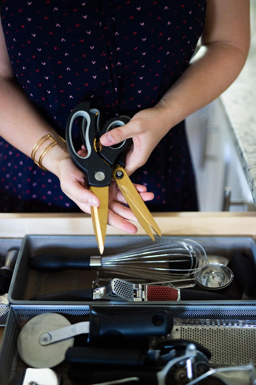 Hands holding set of gold scissors over open kitchen drawer.