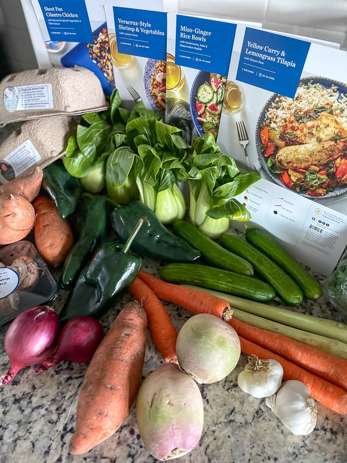 lots of blue apron ingredients all lined up with lots of vegetables