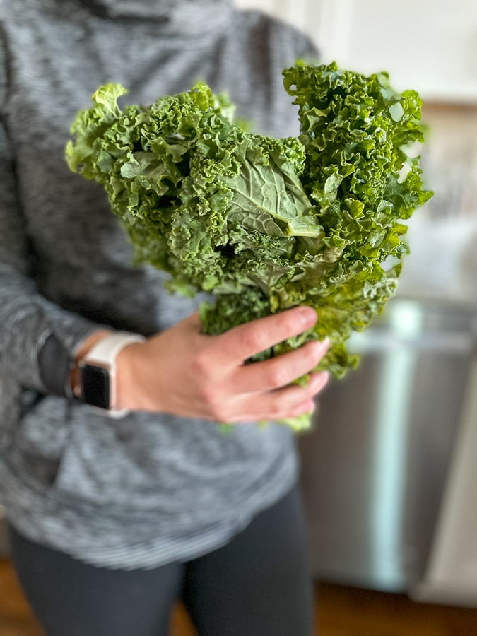 bunch of kale in my hands of Kath Eats