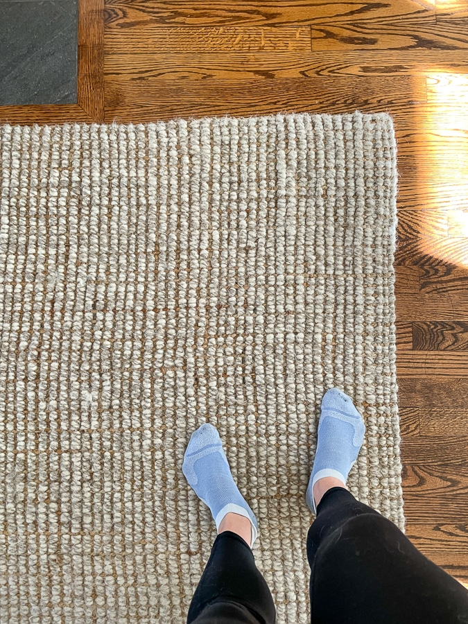 Pottery Barn jute and wool rug with feet in socks