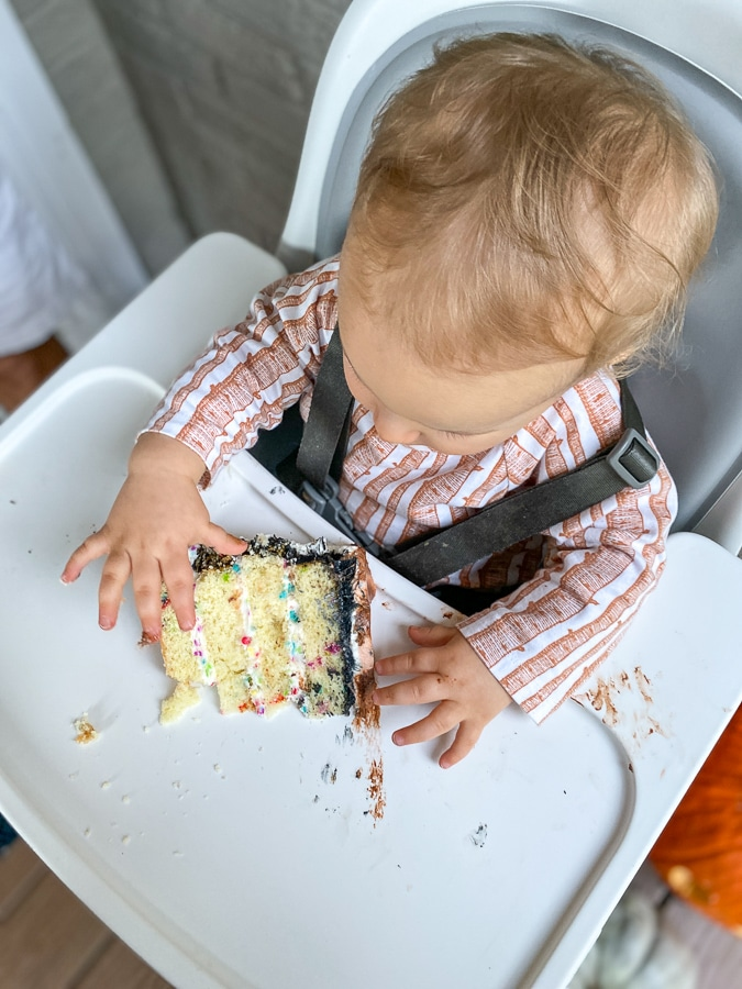baby in high chair eating slice of birthday cake