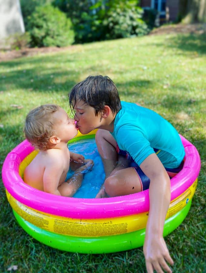 brothers in a kiddie pool kissing