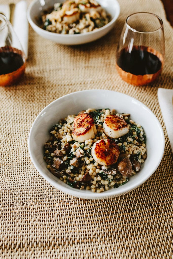 perfectly seared scallops on top of couscous and mushroom dish