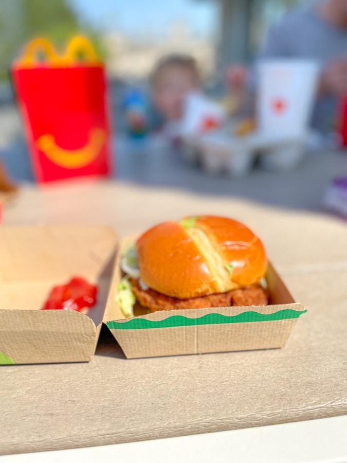 sándwich de pollo mcdonald y comida feliz en el fondo