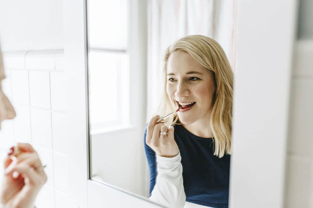 Kath applying lip gloss in mirror